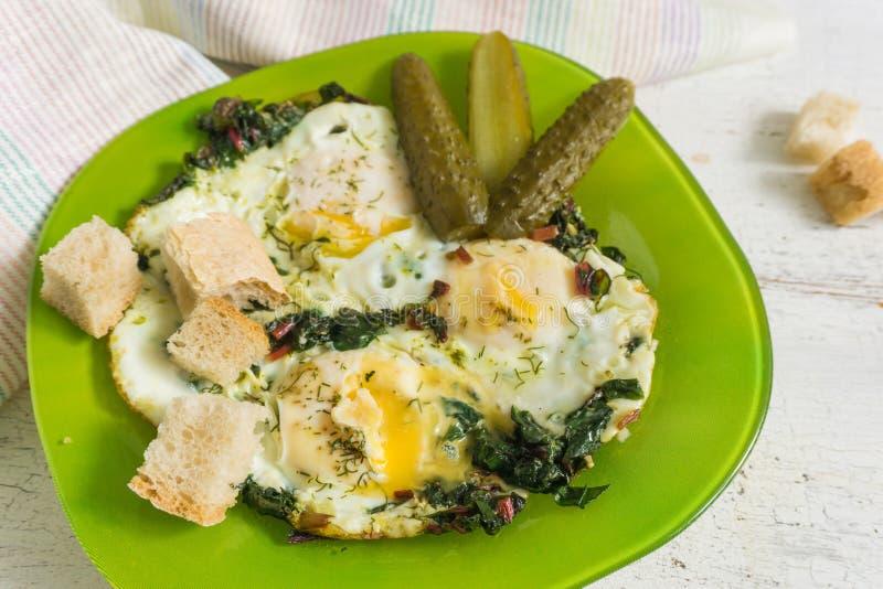 Stekte ägg med charden och marinerade cornichons arkivfoton