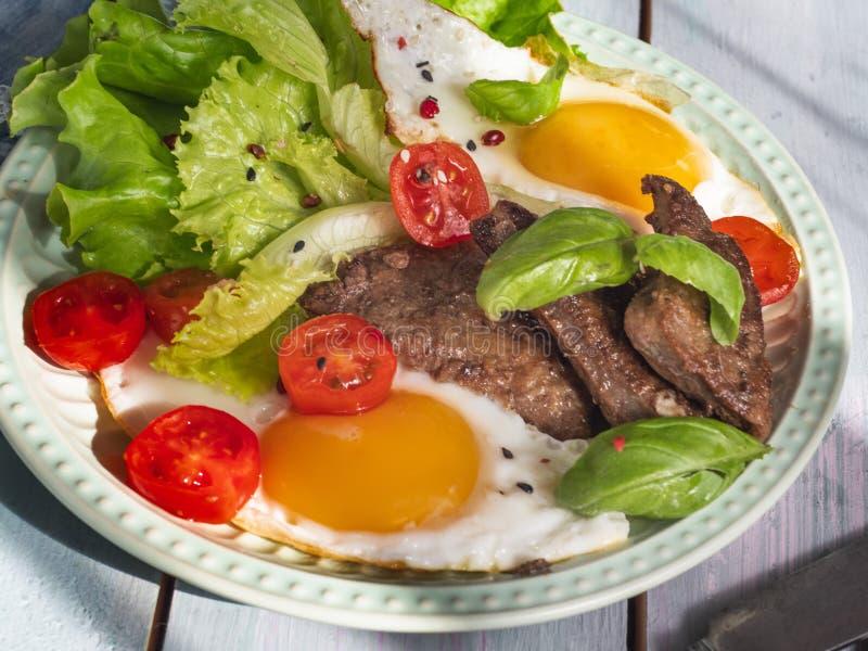 Stekte ägg med grön sallad, körsbärsröda tomater och stekt nötköttleverslut upp skott royaltyfria bilder
