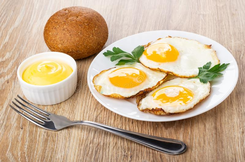Stekte ägg med persilja i plattan, bulle, bunke med majonnäs, gaffel på tabellen arkivfoton