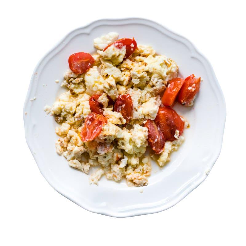 Stekte ägg med skivor av tomater i plattan som isoleras på vit arkivfoton