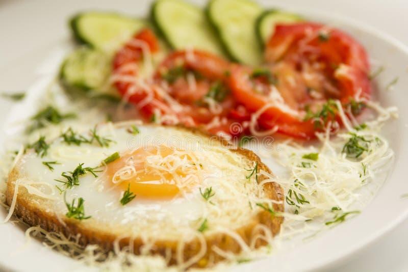Stekte ägg och grönsaker för frukost arkivfoto