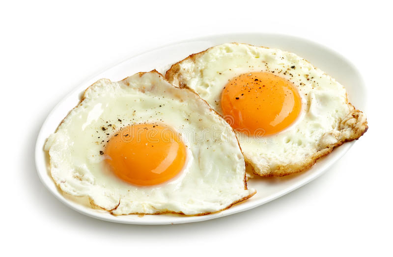 Stekte ägg på vit bakgrund arkivbild
