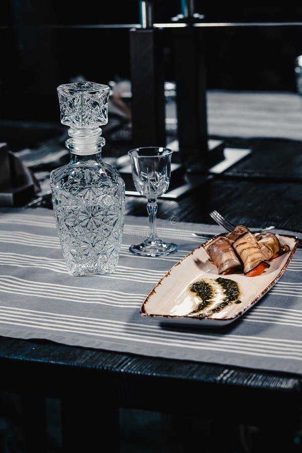 Stekte aubergine som är välfyllda med tomaten och ost på en vit platta med sås På en blå bordduk som göras randig med kniven och arkivbild