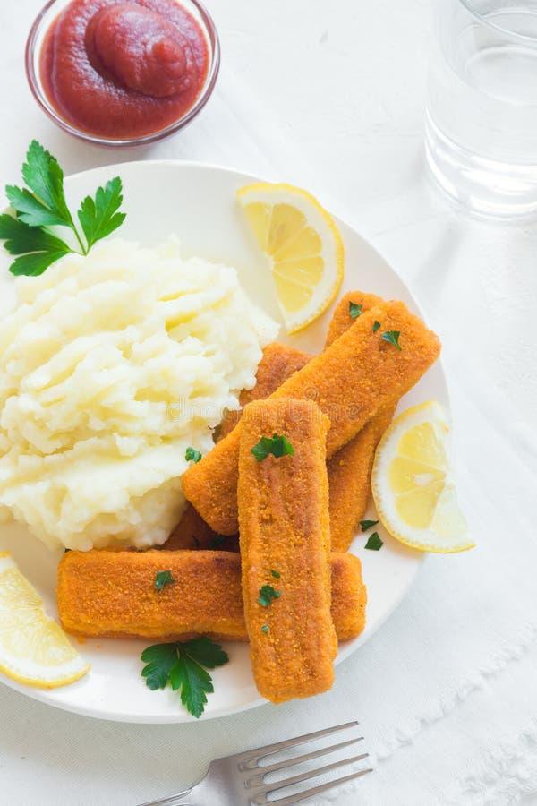 Stekte fiskpinnar, mosade potatisar royaltyfria bilder