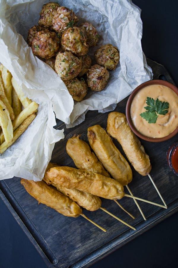 Stekte franska småfiskar, den orange hunden för Ð-¡ och kålkroketter och potatisar med sås och ketchup dekoreras med nya grönsake arkivbild
