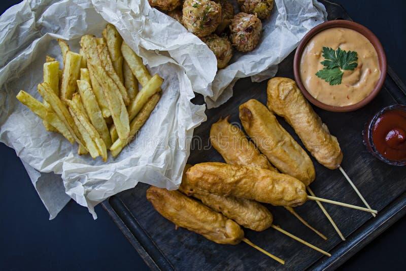 Stekte franska småfiskar, den orange hunden för Ð-¡ och kålkroketter och potatisar med sås och ketchup dekoreras med nya grönsake royaltyfria foton