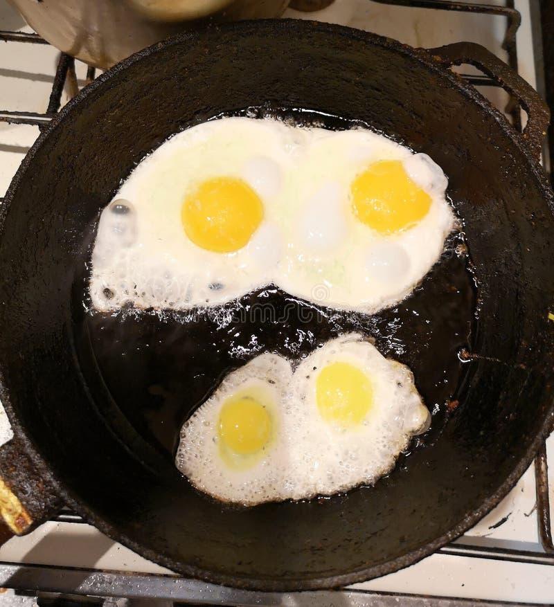 Stekte ?gg i en stekpanna med k?rsb?rsr?da tomater och br?d f?r frukost p? en svart bakgrund arkivbilder