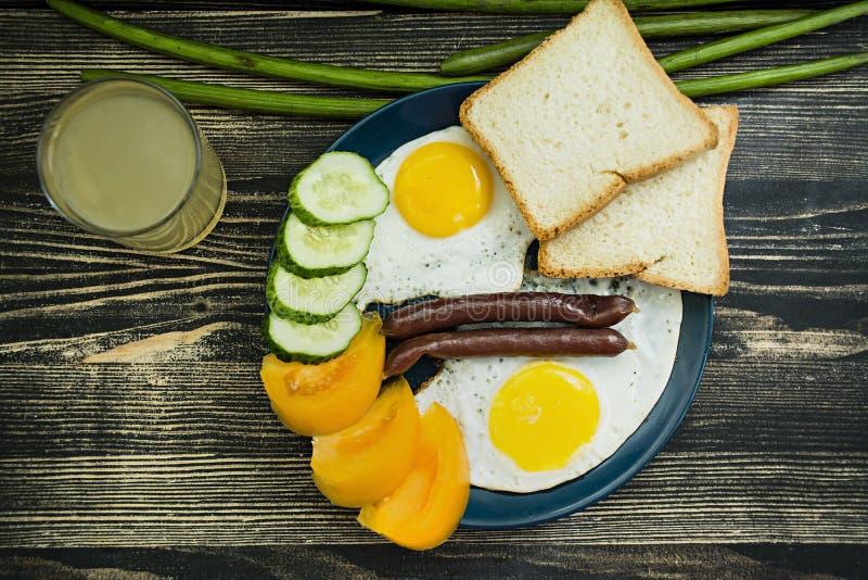 Stekte ?gg i platta med k?rsb?rsr?da tomater, korvar och br?d f?r frukost arkivfoto