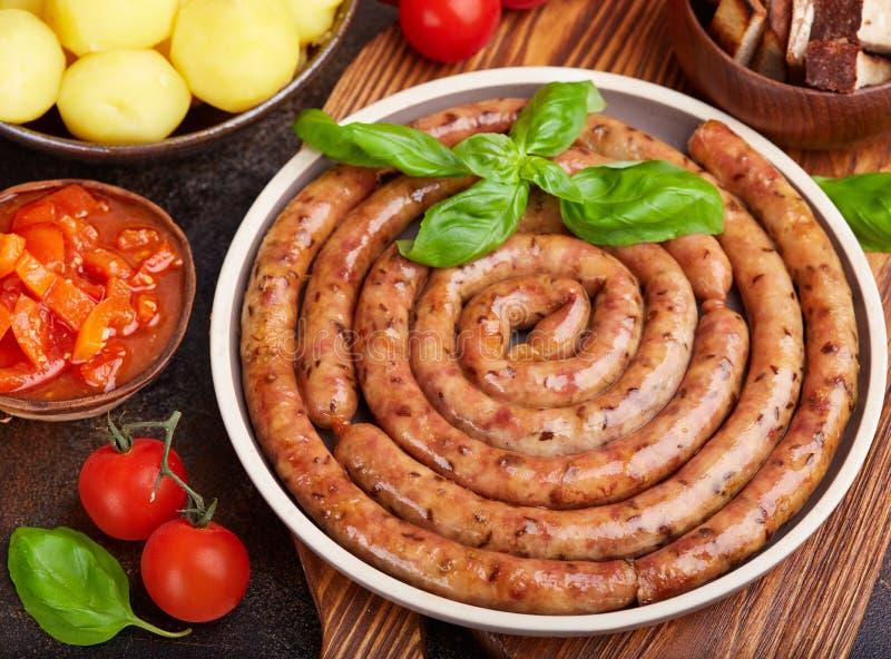 Stekte grisköttkorvar tjänade som med kokta potatisar, sås, tomater och basilikabladet arkivbild