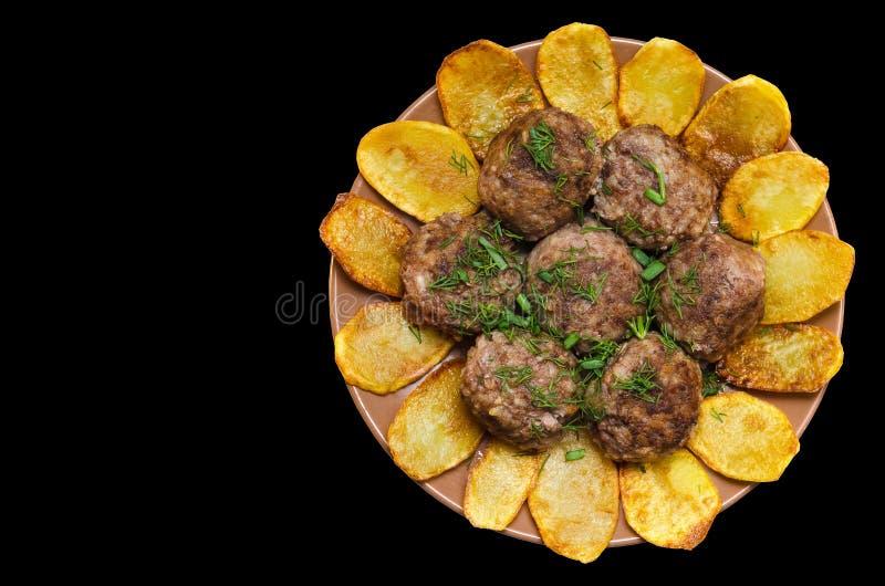 Stekte köttbullar med ris och pommes frites, på en svart bakgrund royaltyfri foto