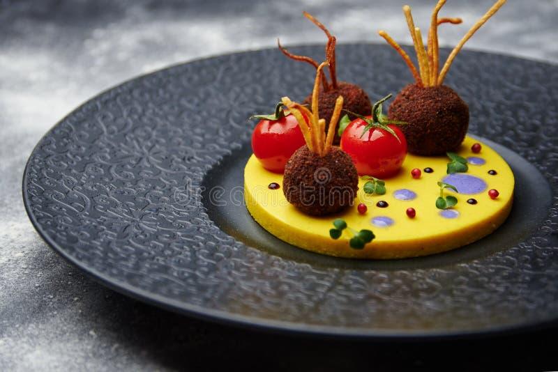 Stekte köttbullar med tomaten på potatisar i en svart platta fotografering för bildbyråer