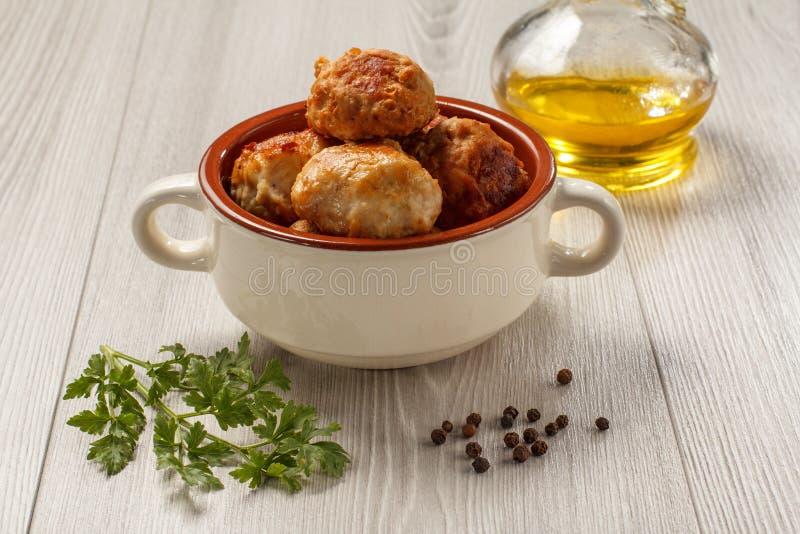 Stekte köttkotletter i den keramiska soppabunken, glasflaska med sunfl royaltyfria bilder
