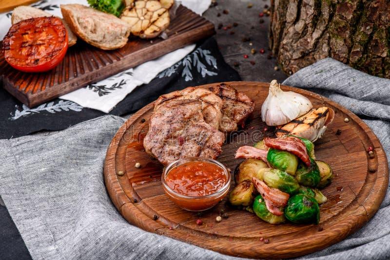 Stekte köttmedaljonger med bräserade Bryssel groddar, grillad vitlök och grillfestsås på runt träbräde royaltyfria bilder
