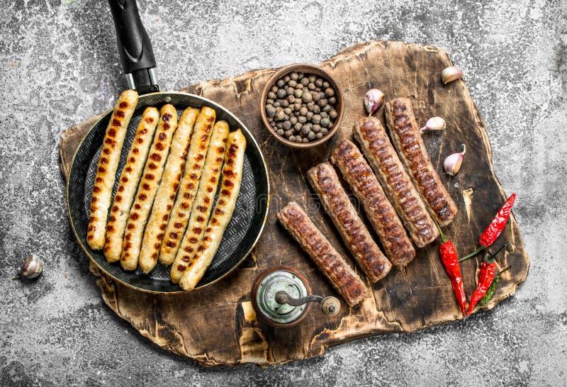 Stekte korvar med kryddor i en stekpanna arkivfoton