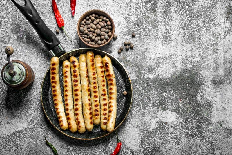 Stekte korvar med kryddor i en stekpanna royaltyfria bilder