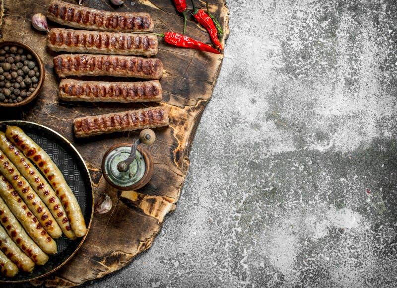 Stekte korvar med kryddor i en stekpanna arkivbilder