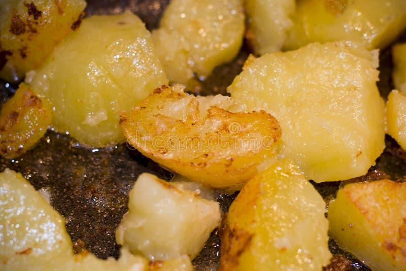 Stekte potatisar i en panna med en guld- brun mineralisk beläggning i grönsakolja Storen specificerar arkivbild