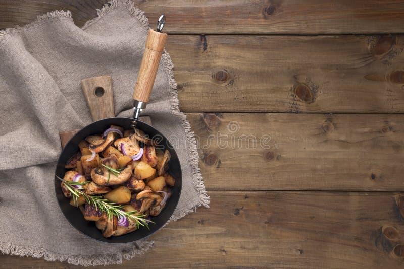 Stekte potatisar i en svart gjutjärnpanna på en träbakgrund Tappningfoto och servett i lantlig stil Fritt utrymme för text som är royaltyfria bilder