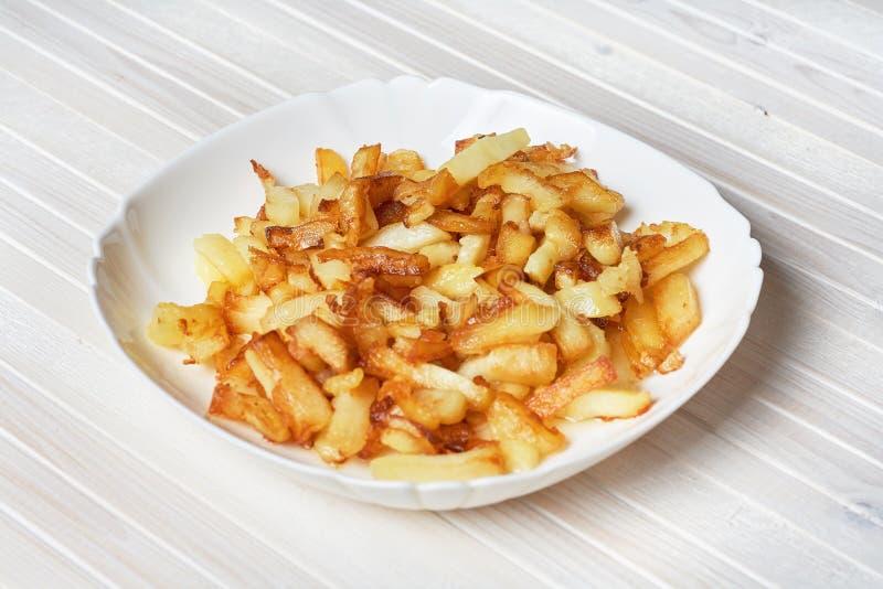 Stekte potatisar i en vit platta på en vit träbakgrund royaltyfri bild