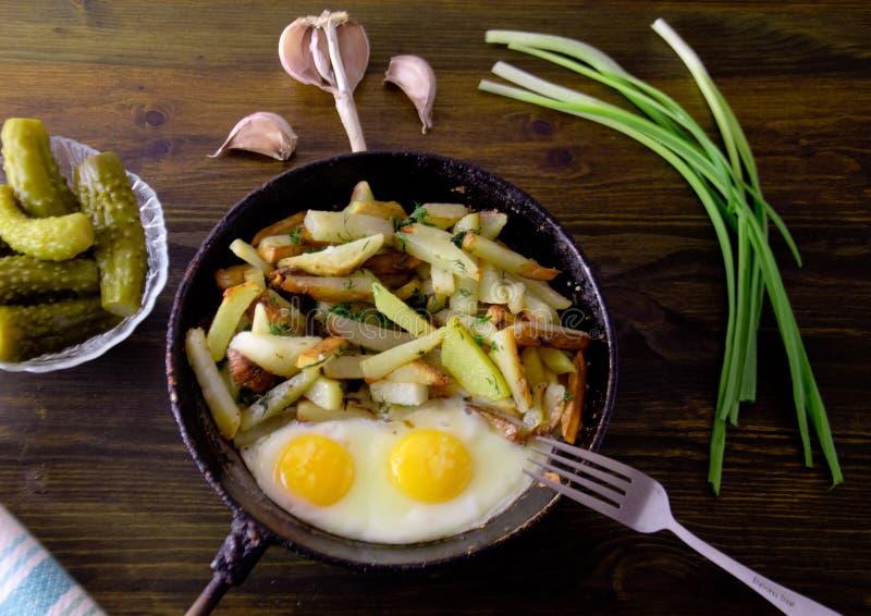 Stekte potatisar med stekte ägg på en stekpanna royaltyfri bild