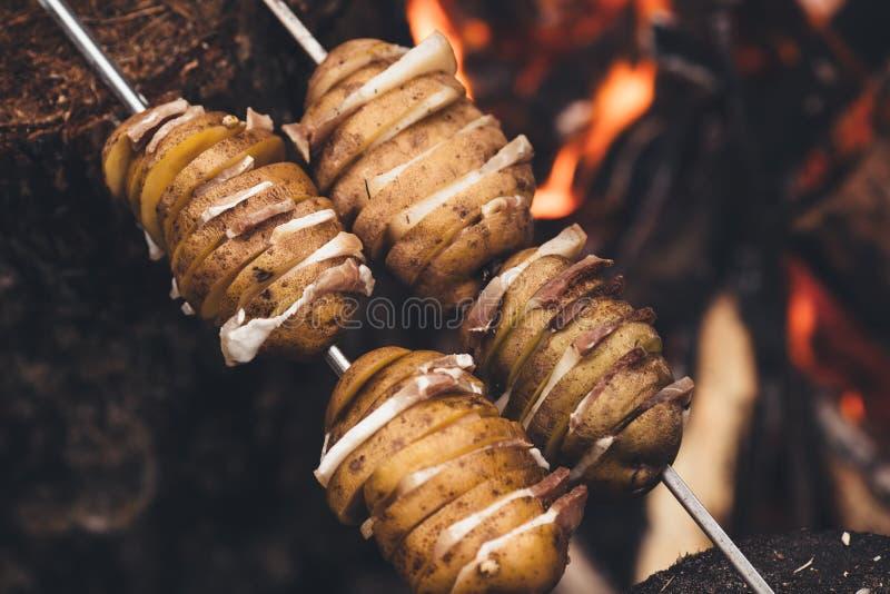 Stekte potatisar med bacon på steknålar Begreppet av att äta outd royaltyfri foto