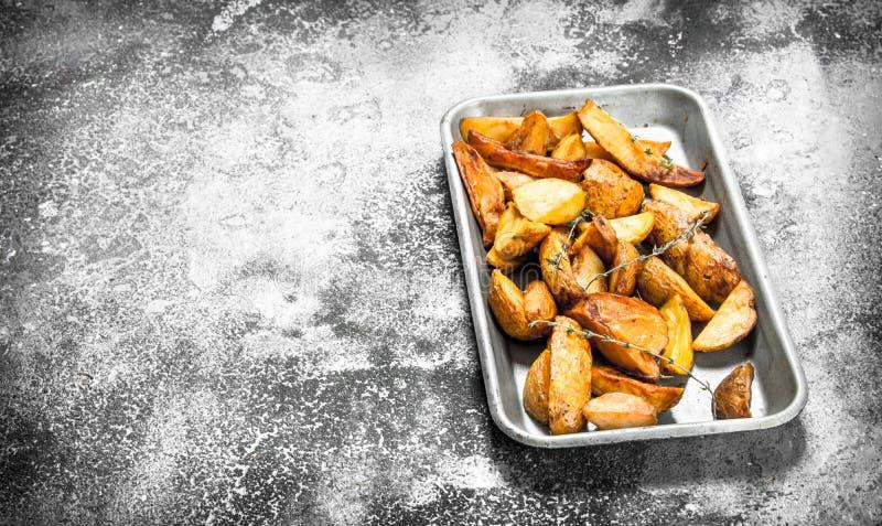 Stekte potatisar på en bakplåt med kryddor och örter fotografering för bildbyråer