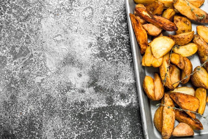 Stekte potatisar på en bakplåt med kryddor och örter arkivbilder