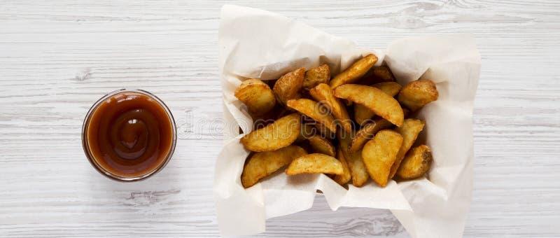 Stekte potatiskilar i pappersask och grillfests?s p? en vit tr?bakgrund ?ver huvudet b?sta sikt, fr?n ?ver arkivfoton