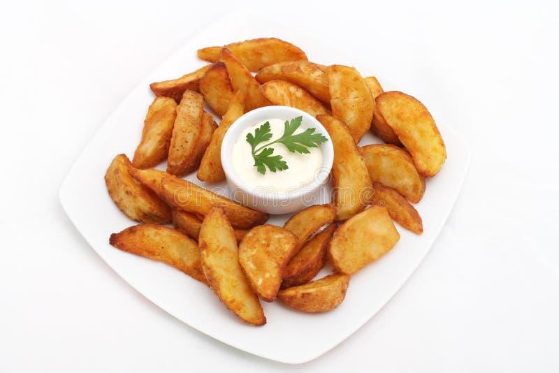 Stekte potatiskilar med vit sås royaltyfri fotografi