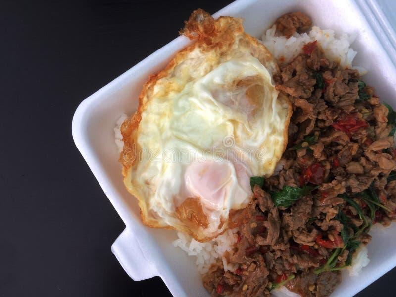 Stekte ris med basilika med det stekte ägget i skumask fotografering för bildbyråer
