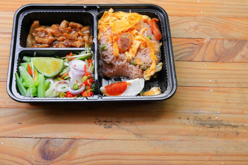 Stekte ris med räkadeg inkluderar mango, ägget, griskött, löken, grönsak i mat för stil för asksvart thailändsk på en wood tabell royaltyfri bild