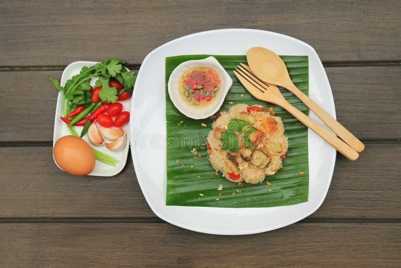 Stekte ris med tilapia stekte serve på banansidor Pålagt en vit platta fotografering för bildbyråer