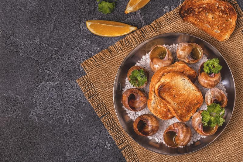 Stekte sniglar med citronen, bagetten och persilja royaltyfria foton