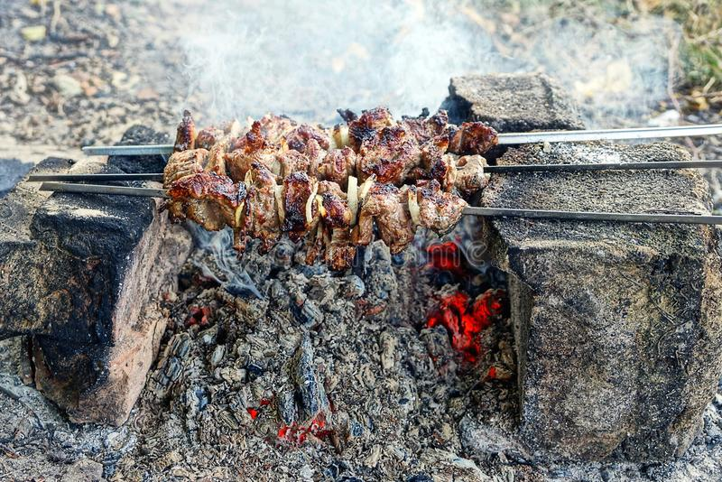 Stekte stycken av kött på steknålar över värmen i röken från branden på stenarna royaltyfria foton