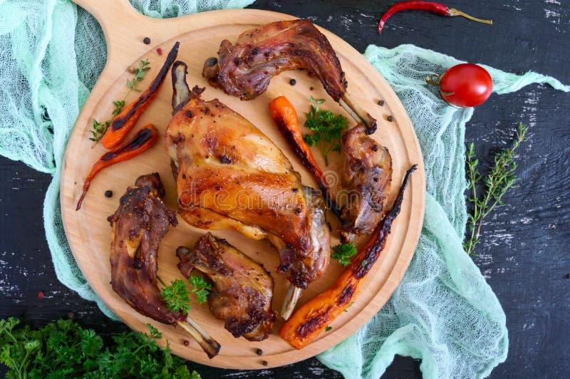 Stekte stycken av kanin med grönsaker på ett trämagasin på en mörk bakgrund royaltyfria bilder