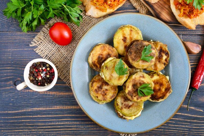 Stekte stycken av zucchinin med majonnäs på en keramisk platta på en trätabell royaltyfria foton