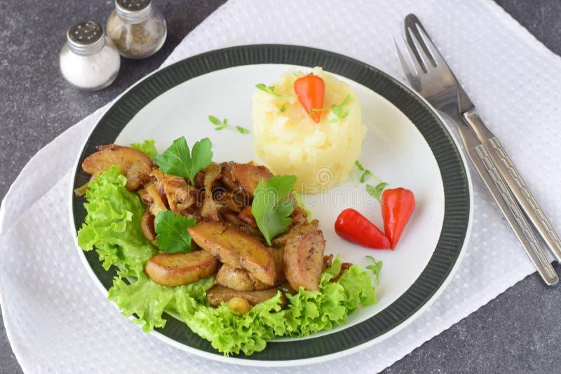 Stekte tjurtestiklar med kräm och örter tjänade som med den mosade potatisen på en vit platta på en abstrakt bakgrund Sunt royaltyfri foto
