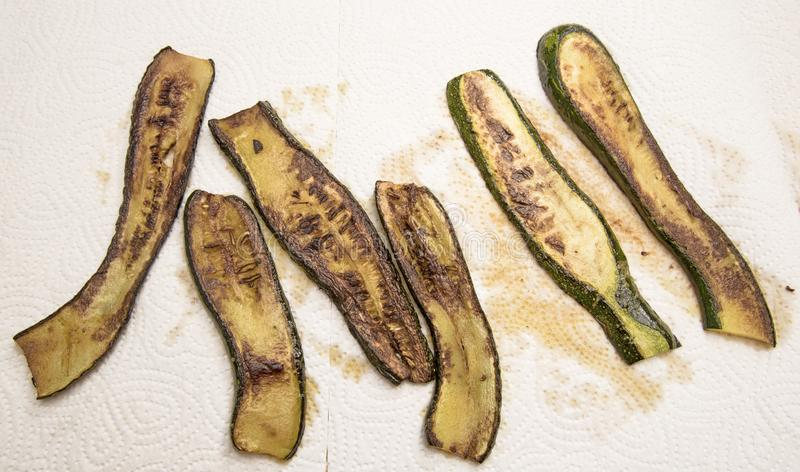 Stekte zucchiniskivor på hushållspapper, läckra grönsaker, medelhavs- stilmatlagning, sikt från över arkivbilder