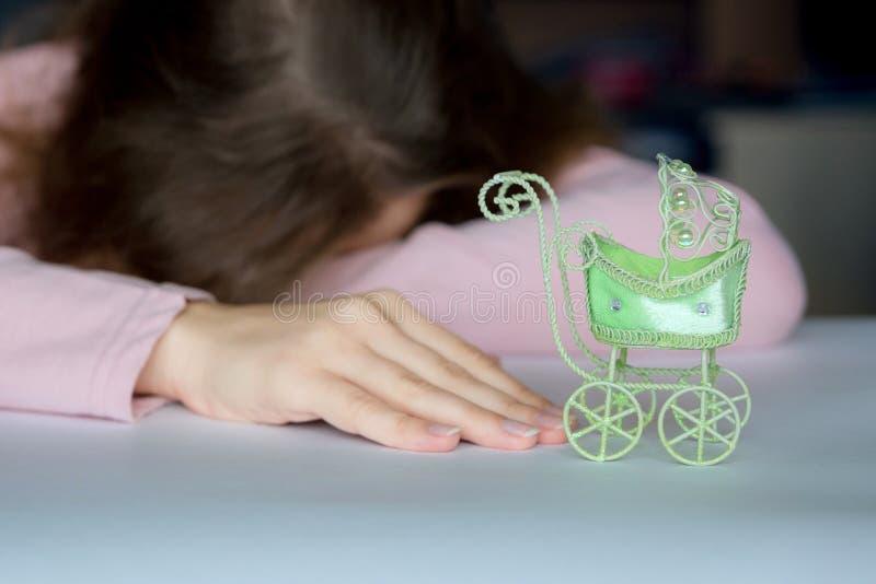 Stel van wanhoop, een verlies van hoop Een vrouw ligt gezicht neer op een lijst, met kanker die voor een stuk speelgoed kinderwag stock afbeeldingen
