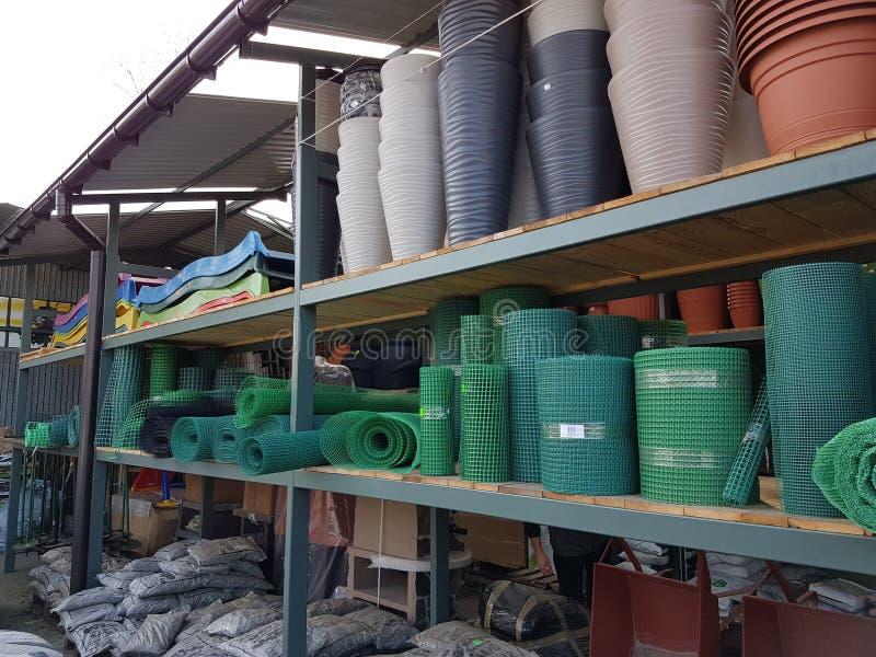 Stelage con los productos plásticos en la acción Productos para cultivar un huerto y los huertos Objetos que facilitan el cultivo imagenes de archivo