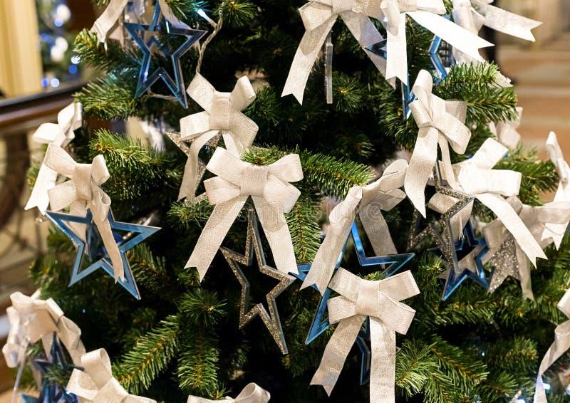 Stella blu d'argento e un nastro bianco su un albero di Natale festivo, Natale dell'elemento della decorazione immagine stock