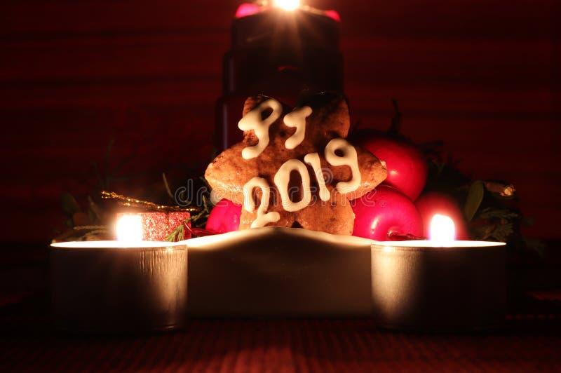 Stella casalinga del pan di zenzero coperta di glassa bianca nei frutti pendenti dei againts del PF 2019 della forma con due cand fotografie stock libere da diritti