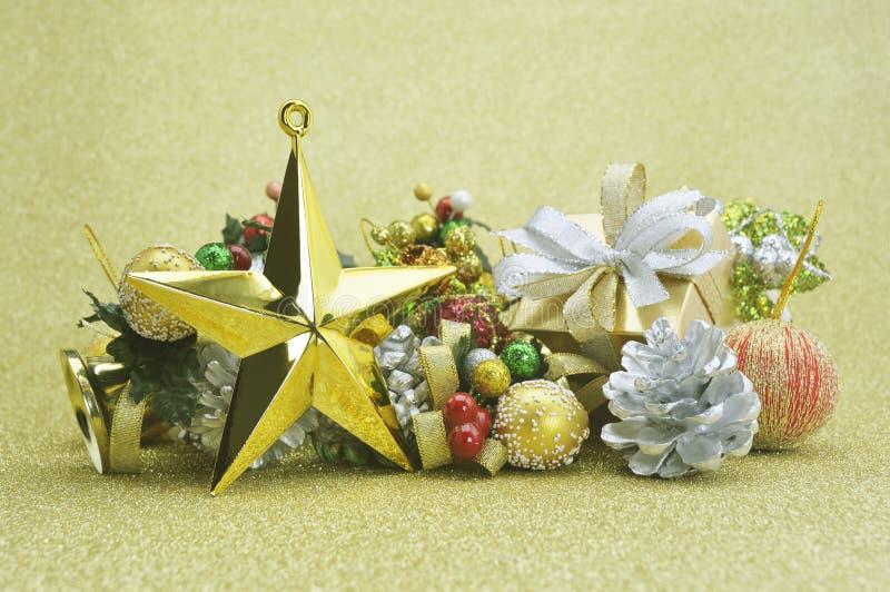 Stella, contenitore di regalo ed ornamento dorati di natale sopra il backgroun dell'oro fotografie stock