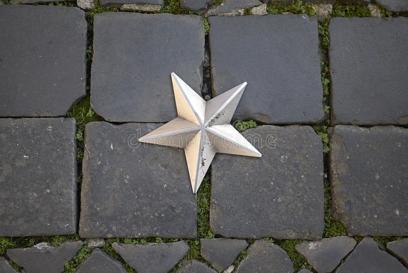 Stella d'argento nella pavimentazione immagine stock