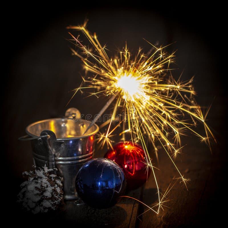 Stella filante bruciante dietro una palla di vetro su un fondo di legno nero immagini stock