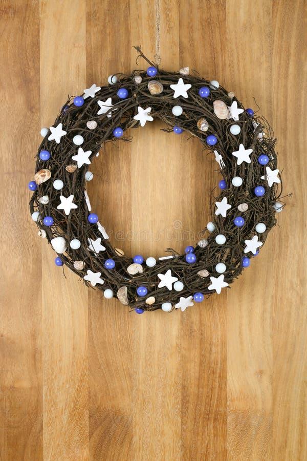 Stelle bianche decorate della corona della porta di Natale e perle blu sulla S immagine stock libera da diritti