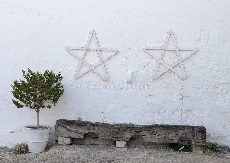 Stelle bianche su una parete dello stucco sopra un vecchio banco di legno fotografia stock