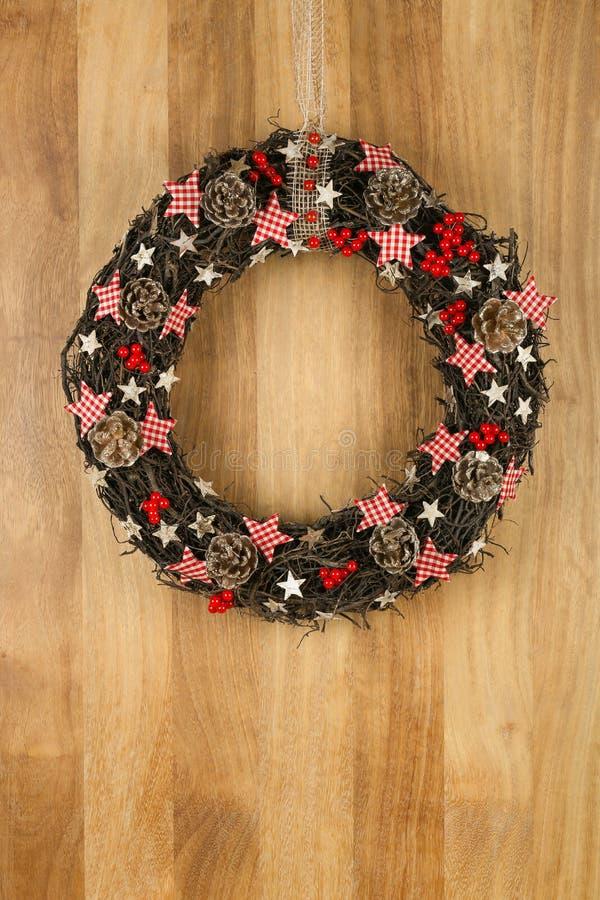 Stelle decorate del percalle della corona della porta di Natale sul BAC di legno di Sapele immagini stock libere da diritti