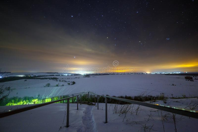 Stelle del cielo notturno con le nuvole Paesaggio di inverno di Snowy immagini stock