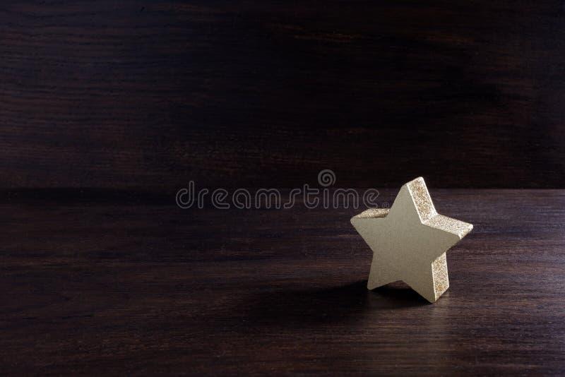 Stelle dorate su fondo di legno scuro, concetto di valutazione superiore fotografia stock